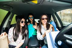 Young women returning from the shopping inside car. Young girls riding car and returning from shopping. stock photo