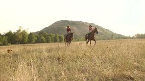Young girls is riding a horse in summertime. Two girls in cowboy hats, jeans and shirts jump horseback in the field at sunset, slow motion. Wide shot. Young stock video footage
