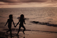 Young girls running on the beach Royalty Free Stock Images