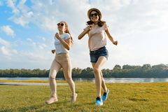 Young girls are running. Teenagers having fun on the green lawn in the park, enjoying sunny summer day, golden hour stock photo