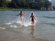 Young girls running to the sea. Summer beach view with young happy girls running to the sea water Stock Images