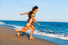 Young girls running towards waves. Royalty Free Stock Photo