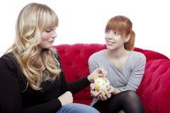 Young girls save money in piggybank Stock Photos