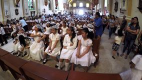 Young girls seated assembled to receive sacrament of communion. San Pablo City, Laguna, Philippines - July 6, 2017: Young girls seated assembled to receive stock video footage