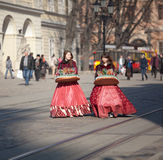 Young girls sell sweets. Lviv, Ukraine - March 17: Unindentified young girls, wearing 19th century dresses, sell candy on March 17, 2012 in Lviv, Ukraine. City Royalty Free Stock Image