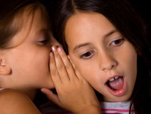 Young girls sharing a secret. Two beautiful young girls sharing a secret royalty free stock image