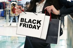 Young girls with shopping bags in store. The inscription Black Friday on a white package. Girl looks at their purchases in your royalty free stock photography