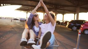 Young girls in shopping carts giving high five. Near shopping mall. They very happy and cheerful stock footage