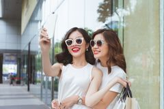 Young girls shopping together and make a selfie with a smartphone.  royalty free stock image