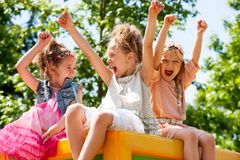 Young girls shouting and raising arms outdoors. Royalty Free Stock Image