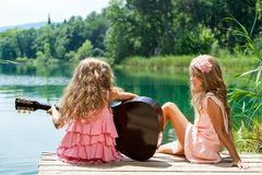 Young girls singing together with guitar. Stock Photos