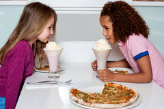 Young girls sipping strawberry shake Stock Photo