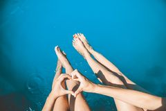 Young girls sit on the edge of swimming pool and chat with their feet in the water and hold their hands in heart. Summer royalty free stock photos