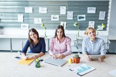 Young girls are sitting at the office at the table. Royalty Free Stock Image