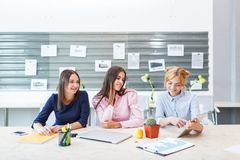 Young girls are sitting at the office at the table. Royalty Free Stock Images