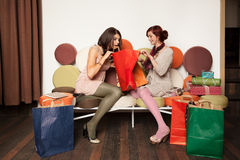 Young girls on sofa with shopping bags Royalty Free Stock Photos