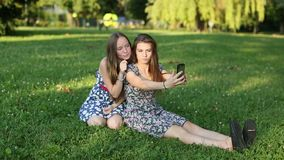 Young girls sitting in a clearing talking and take a selfie together. stock video