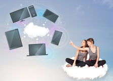 Young girls sitting on cloud enjoying cloud network service Stock Photo