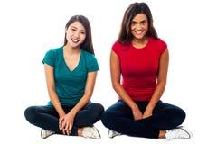 Young girls sitting on the floor, studio shot. Two young girls sitting on the floor, legs crossed Stock Photos