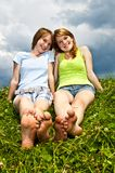 Young girls sitting in meadow. Two young teenage girl friends sitting barefoot on summer meadow Royalty Free Stock Photography