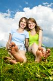 Young girls sitting in meadow. Two young teenage girl friends sitting barefoot on summer meadow Royalty Free Stock Image