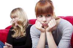 Young girls sitting on red sofa upset Stock Images