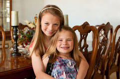 Young girls sitting at wood dining table. Young girls sitting at wood finished dining room table with decorations stock photo