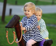 Young girls sitting on wooden horse Royalty Free Stock Images