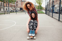 Young girls skating in basketball court Royalty Free Stock Image