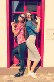 Young girls smiling and posing in front of the door Stock Photography