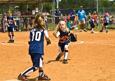 Young Girls Softball. Teams of 6-7 year old girls during a softball game.  Making a play to get the runner out Royalty Free Stock Images