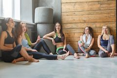 Young girls in sportswear having rest after fitness training. Girls in sportswear having rest after fitness training. Group of young fit women sitting and Royalty Free Stock Photos