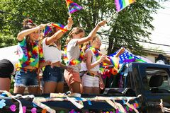 Young girls standing and waving pride flags in back of a truck during Gay Pride Parade