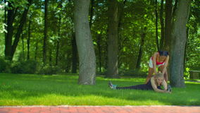 Young girls stretching before fitness workout at green grass in park. Two women doing stretching exercise outdoor at summer. FItness women stretching stock footage