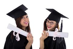 Young girls in student mantle with diploma. Two young girls in student mantle hold the diploma with pink ribbon in her hand Stock Images