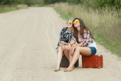 Young girls with sunglasses waiting on road Stock Photography