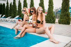 Young girls in swimsuits, sunbathing on poolside Stock Photos