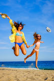 Young girls in swimwear jumping on beach. Royalty Free Stock Photos