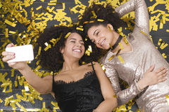 Young girls taking self portrait with mobile phone. Lying together on a floor covered in golden confetti Stock Photos