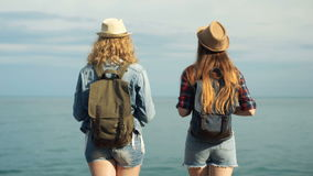 Young girls travelers with a backpacks going on a beautiful beach.  stock video footage
