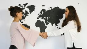 Young girls twins shaking hands and embracing. On the background of the world map stock video