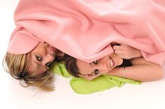 Young girls under blanket smile Royalty Free Stock Photography