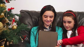 Young girls using a digital tablet near Christmas tree stock video