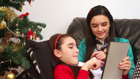 Young girls using a digital tablet near Christmas tree. Christmas time, two smiling young girls using a digital tablet, near Christmas tree illuminated stock video