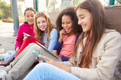 Young Girls Using Digital Tablets And Mobile Phones In Park Stock Image