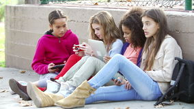 Young Girls Using Digital Tablets And Mobile Phones In Park. Group of young girls sitting by wall in playground using digital tablet and mobile phones.Shot on stock footage