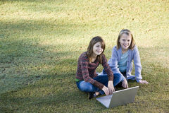 Young girls using laptop on grass. Two young friends (10 and 11 years) using laptop together outdoors in park Royalty Free Stock Photo