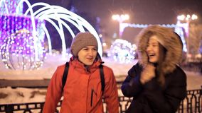 Young girls walk in the winter on the central square of the city near the Christmas tree. Holiday, snow, joy.  stock video