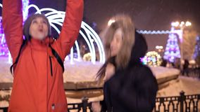 Young girls walk in the winter on the central square of the city near the Christmas tree. Holiday, snow, joy.  stock footage