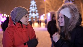 Young girls walk in the winter on the central square of the city near the Christmas tree. Holiday, snow, joy.  stock video footage